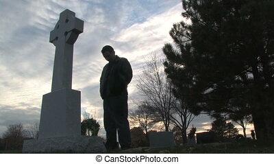 Man in Cemetery - Silhouete of a man standing at a grave...