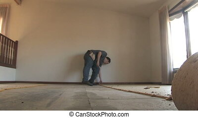 Man Removing Carpet - A handyman tears up carpet padding...