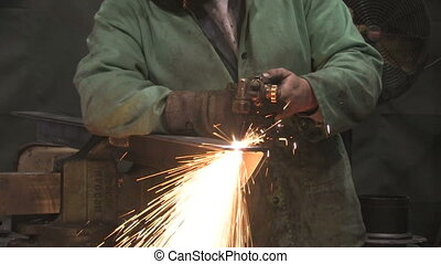 Man Using Blowtorch 1 - A man uses a blowtorch to cut a...