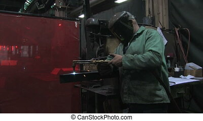 Man Using Blowtorch 3 - A man uses a blowtorch to cut a...