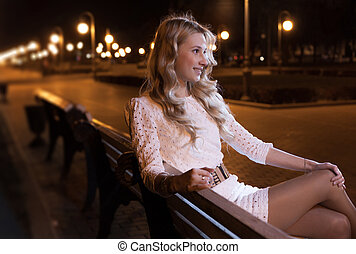women on bench at night - blond haired female having rest on...