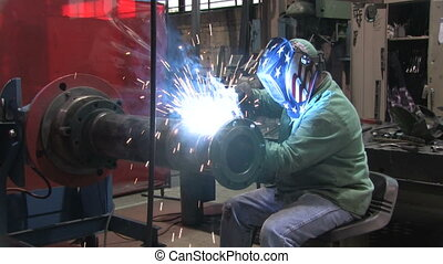Man Welding in Factory 1 - A worker welding in a factory as...