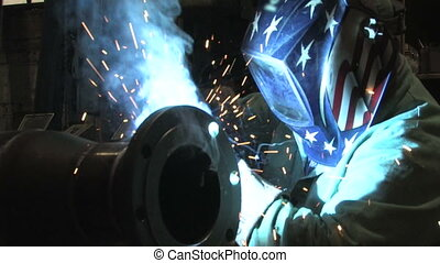Man Welding, Close Up 1 - A worker welding in a factory as...