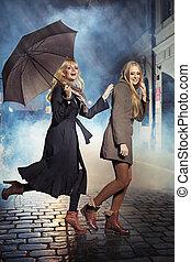 Two blonde ladies running during rain