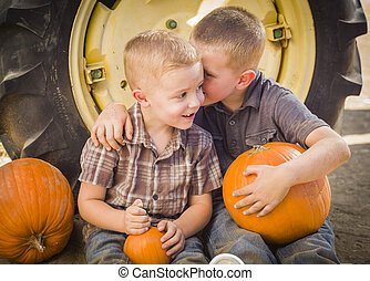 Two Boys Sitting Against a Tractor Tire Holding Pumpkins and Whispering Secrets in Rustic Setting.