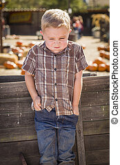 Frustrated Little Boy at Pumpkin Patch Farm Standing Against Old Wood Wagon.