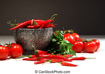 Red peppers and tomatoes with granite bowl on dark...