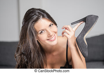 Attractive woman holding up an elegant shoe - Attractive...