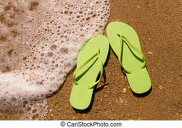 Flip Flops in the water - Bright green flip flops laying on...