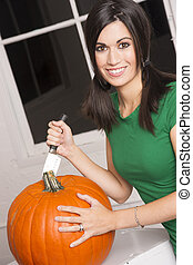 Excited Woman Cutting Carving Halloween Pumpkin...