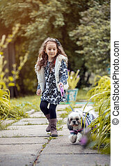 Walk in park - cute girl holding her dog on leash