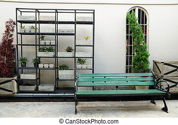 Outdoor decoration with green chair and many plant pots on...