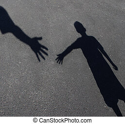 Helping Hand with a shadow on pavement of an adult hand...