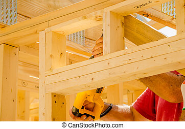 Building contractor worker using a reciprocating saw to cut...