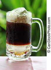 Root beer float, a tasty summer treat.on Green tree...
