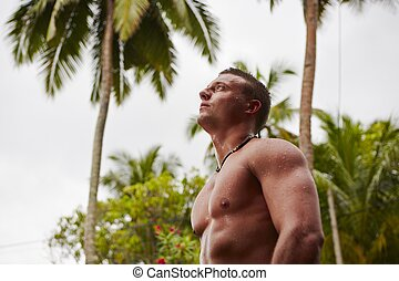 Man in the rain - Muscular man is under the palm tree in the...