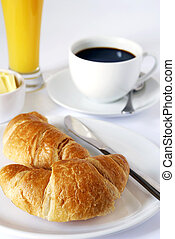 continental breakfast of coffee, orange juice and croissants