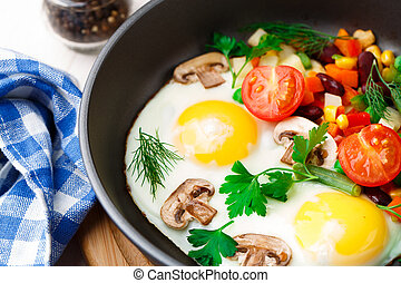 Fried eggs in a pan with vegetables and mushrooms