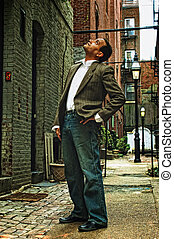 looking in the alley - ethnic american male standing in...
