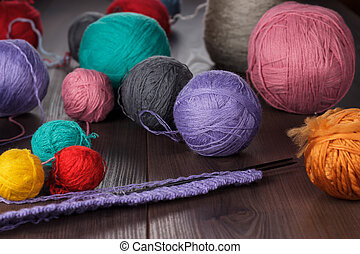 knitting needles and balls of threads on wooden table