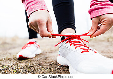 Woman runner tying sport shoes Walking or running legs,...
