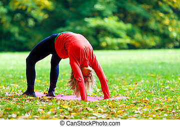 Young woman exercising yoga autumn - Young happy woman doing...
