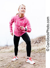 Woman runner exercising and stretching, autumn nature outdoors
