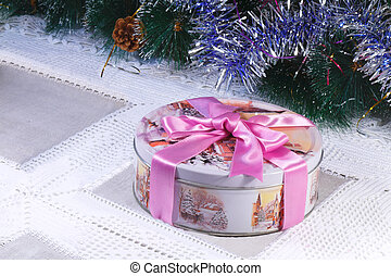 Beautiful box with a gift for Christmas, with the image of winter scenes, tied with a pink ribbon is Located near the decorated Christmas tree.