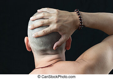 Buddhist Feels Shaved Head - Close-up of a buddhist man...
