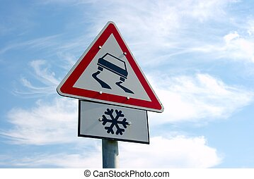 Traffic sign warns about slippery road ahead