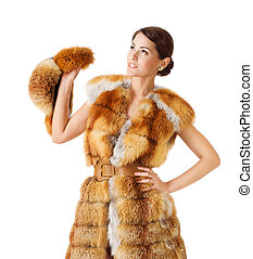 Woman in fur coat, holding fur hat. Isolated white background.