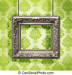 Silver picture frame hung against floral wallpaper...