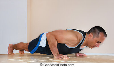 Man Doing Push Ups - Strong man in tank top doing push ups...