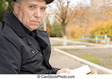 Close up portrait of an elderly man in an overcoat and hat...