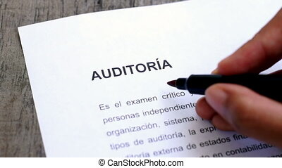 Circling Audit with a pen - A person Circling Audit with a...