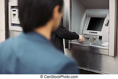 Robber follows his victim - Man withdrawing cash at an ATM...