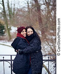 Sisters Hugging in This Cold Winter Park