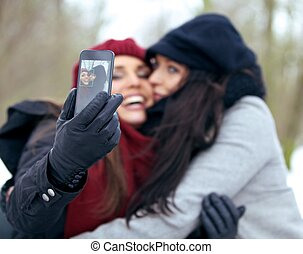 Fun Women Outdoors Taking Pictures with a Smart Phone