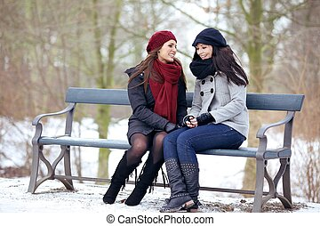 Two Bestfriends Sitting on a Park Bench - Two bestfriends...