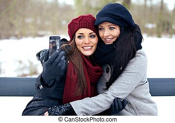 Two Friends Taking Picture of Themselves Using a Smartphone