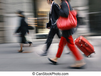 People with a red bag and a suitcase walking down the...
