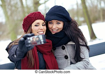 Two Beautiful Women with Camera Phone in a Park