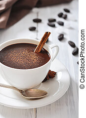 Hot Chocolate in cup with cocoa powder and cinnamon stick on...