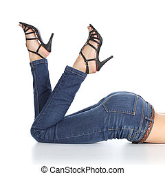 Woman legs lying with jeans and sandal heels pointing up...