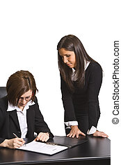 Signing the contract - Two businesswomen signing a contract...