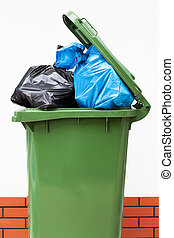 Full green dustbin - A green dust bin full of rubbish sacks