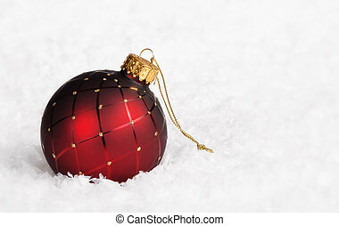 Red Christmas ball ornament with golden trim on snow...