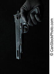Gun and a Hand on a Black Background