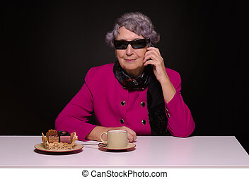 Gray-haired lady speaks by mobile phone