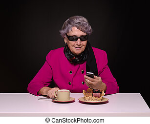 Gray-haired lady dials on a mobile phone